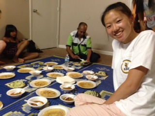 CHI participant, Jane, enjoys both food and friends in a Burmese house church.
